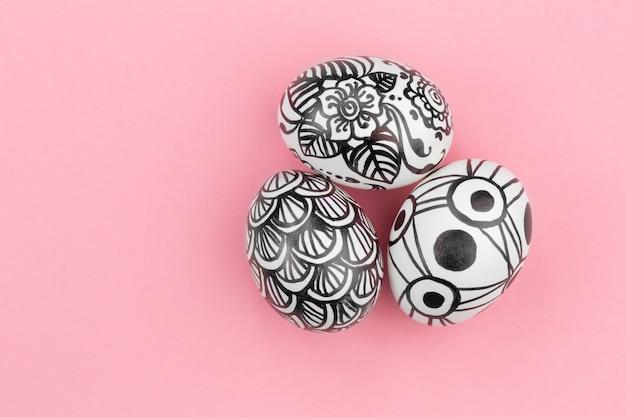 Ovos de páscoa são pintados em preto e branco, abstração, estão nas proximidades. ovos de páscoa pintados em um fundo rosa. copie o espaço. postura plana.