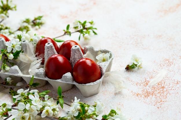 Ovos de páscoa vermelhos com brunches de flores de primavera no fundo bege claro.