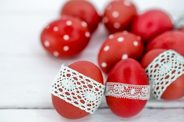 Ovos de páscoa vermelhos em fita de renda branca amarrada, close-up, deitado sobre uma madeira branca