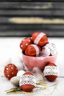 Ovos de páscoa vermelhos em fita de renda com nós de madeira, close-up, natureza morta