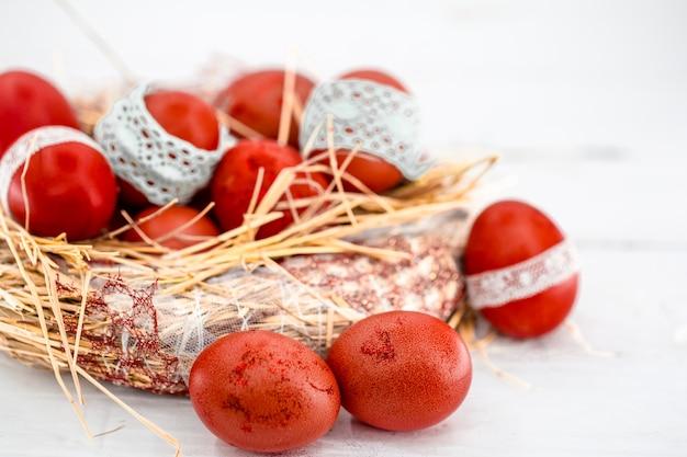 Ovos de páscoa vermelhos em um ninho de feno, amarrados em uma fita de renda, close-up, deitado sobre uma madeira branca