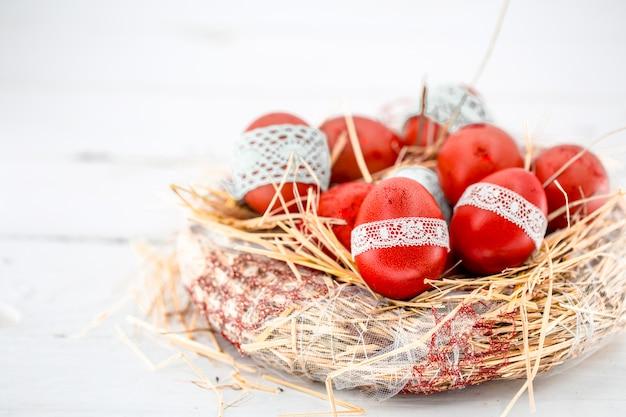 Ovos de páscoa vermelhos em um ninho de feno
