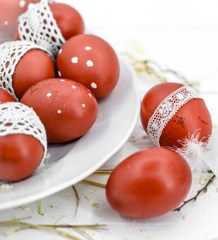 Ovos de páscoa vermelhos em um prato branco e em uma fita de renda branca amarrada, close-up