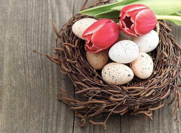 Ovos de pássaros em ninhos com flores de tulipa em fundo de madeira vintage