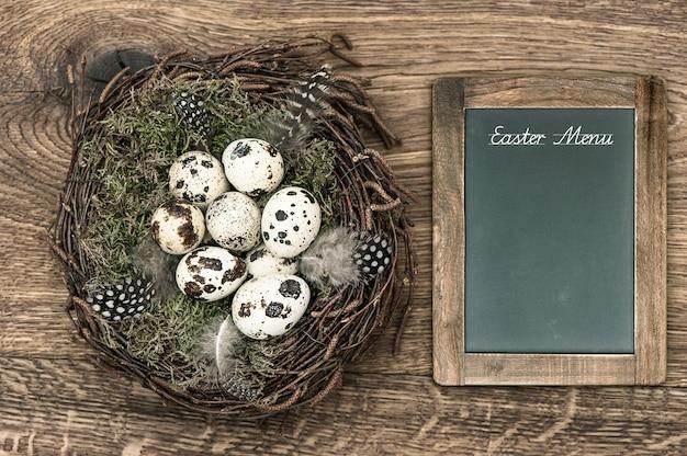 Ovos de pássaros no ninho em fundo de madeira rústico. decoração de páscoa vintage com quadro-negro e texto de exemplo menu de páscoa
