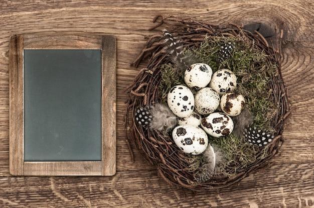 Ovos de pássaros no ninho em fundo de madeira rústico. decoração vintage de páscoa com quadro negro para o seu texto