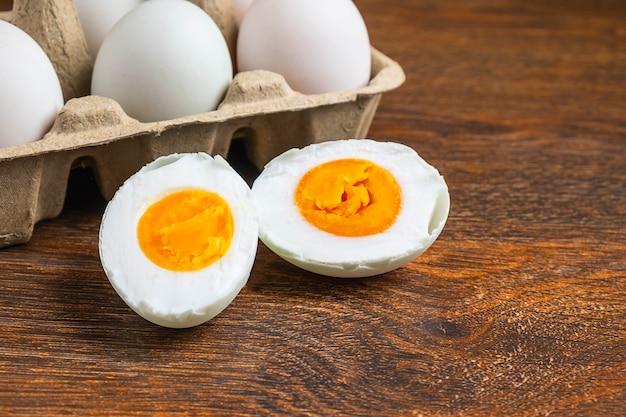 Ovos de pato branco e comida de ovo salgado em uma mesa de madeira