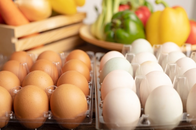 Ovos de pato e frango são colocados em uma mesa de madeira com vários legumes