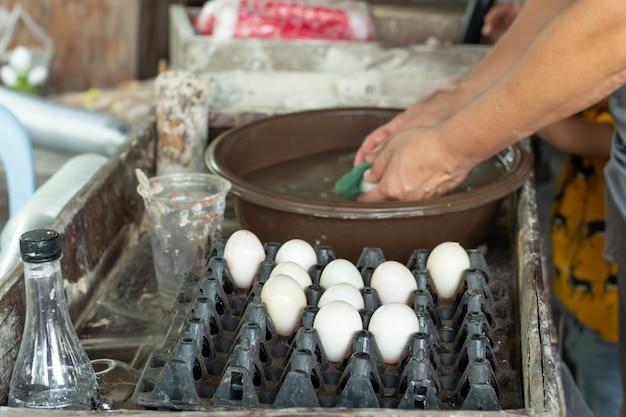 Ovos de pato são lavados e colocados em uma bandeja