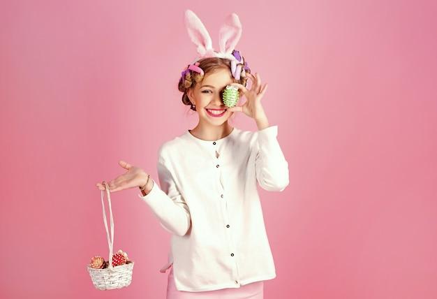 Ovos de pintura adolescente. páscoa menina em orelhas de coelho.