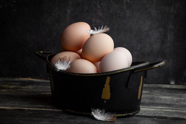 Ovos de vista lateral em panela com penas no fundo escuro de madeira. horizontal