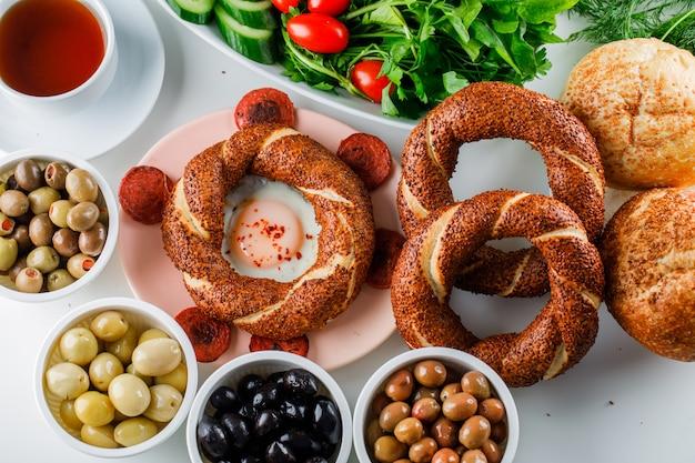 Ovos de vista superior com linguiça no prato com uma xícara de chá, pão turco, salada na superfície branca