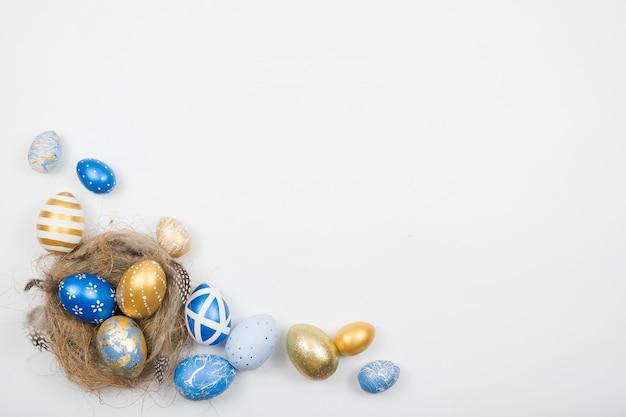 Ovos decorados da páscoa dourada no ninho isolado na superfície branca. conceito mínimo de páscoa.