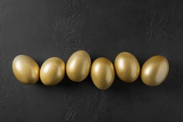 Ovos dourados coloridos galinha no preto. conceito escuro de páscoa. vista de cima.