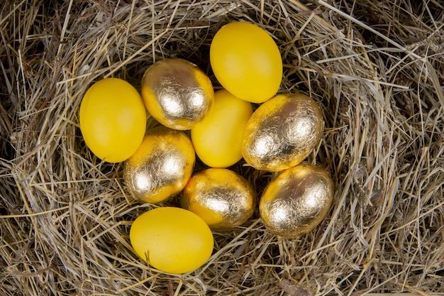 Ovos dourados e amarelos em uma vista superior do ninho. páscoa do conceito.