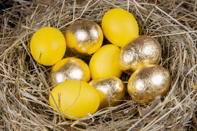 Ovos dourados e amarelos em uma vista superior do ninho. páscoa do conceito. Foto Premium
