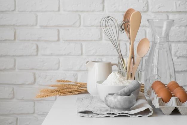 Ovos e arranjo de utensílios de cozinha vista frontal