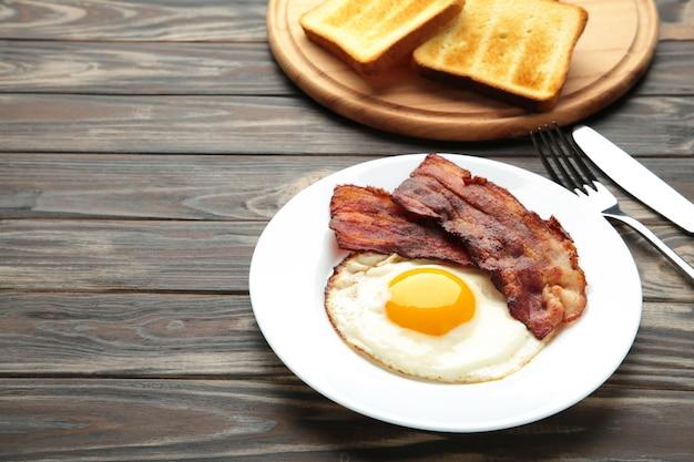 Ovos e bacon no café da manhã na superfície marrom
