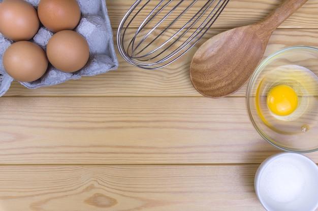 Ovos e batedores frescos na mesa de cozinha, conceito saudável da proteína do café da manhã da vista superior.