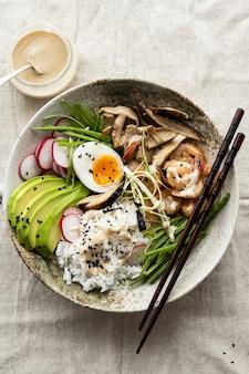 Ovos e camarões servidos com molho de tahine em estilo fotográfico plano