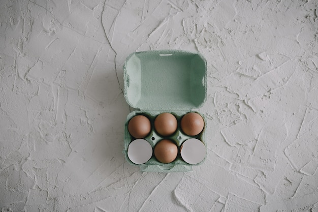 Ovos e cascas de ovo em uma caixa sobre a mesa