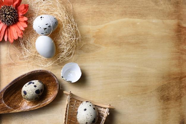Ovos e flores de ninho no fundo de madeira.