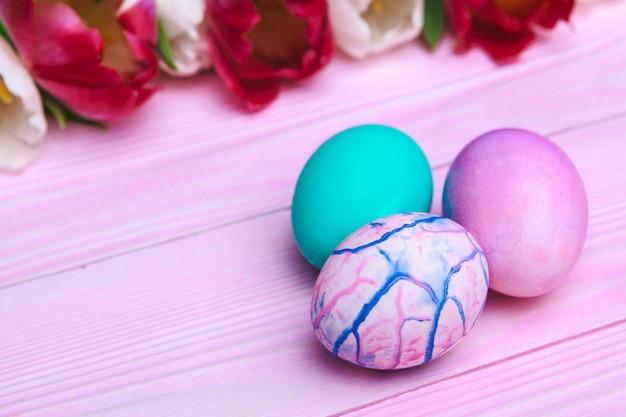 Ovos e tulipas coloridos da páscoa sobre a madeira cor-de-rosa.