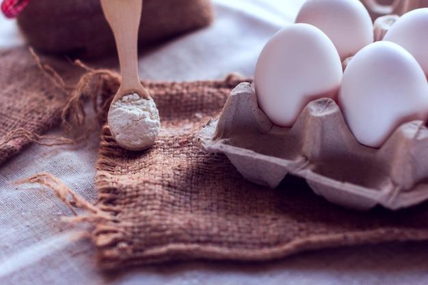 Ovos e uma colher com farinha em um saco