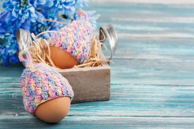 Ovos em chapéus de malha, flores