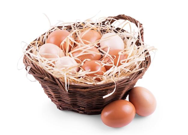 Ovos em palha e em uma cesta em um fundo branco