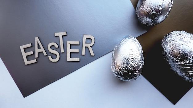 Ovos em papel alumínio em fundo prata. bandeira do conceito de páscoa. com texto de páscoa