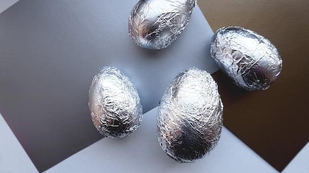 Ovos em papel alumínio em fundo prata. banner de conceito de páscoa