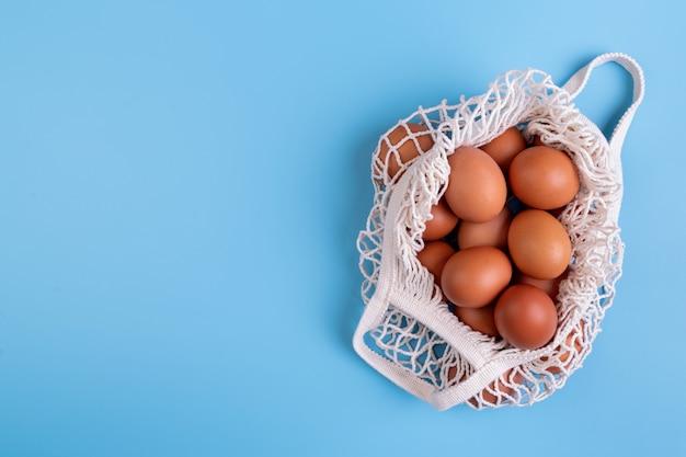 Ovos em um saco de rede de compras branco isolado no fundo azul vista superior plana leigos com espaço de cópia