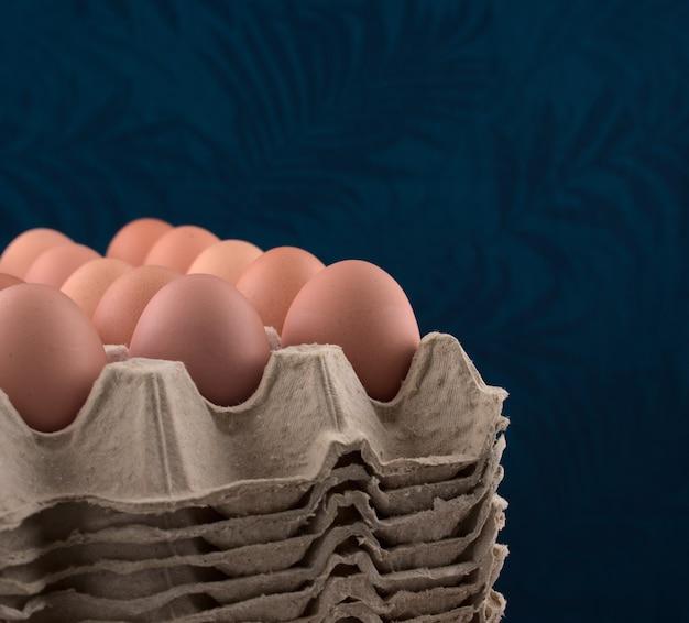 Ovos em uma caixa de papelão contra um fundo azul de tecido vintage.