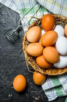 Ovos em uma cesta com um batedor e guardanapo. sobre fundo preto rústico.