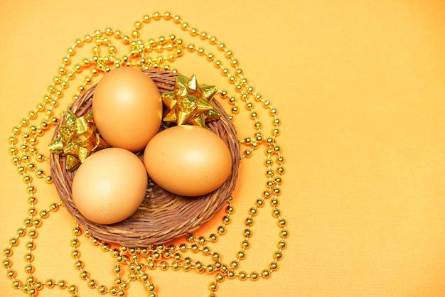 Ovos em uma cesta em uma mesa amarela, em uma decoração de ouro