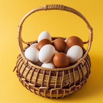 Ovos em uma cesta sobre fundo amarelo.