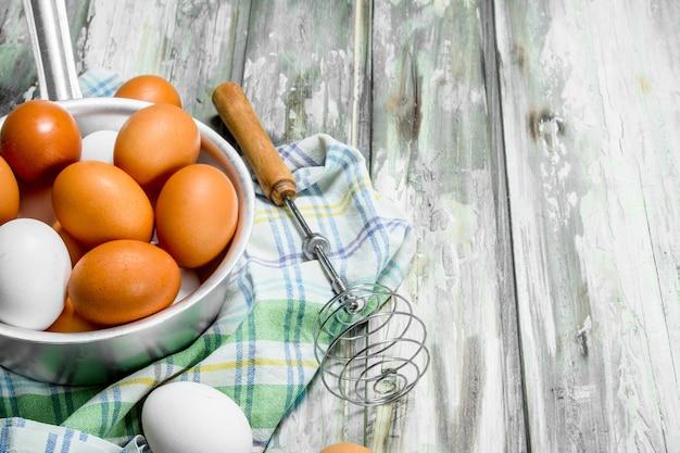 Ovos em uma panela com um batedor no guardanapo. sobre um fundo rústico.