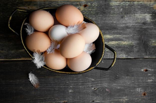 Ovos em uma panela com vista superior de penas em um fundo escuro de madeira