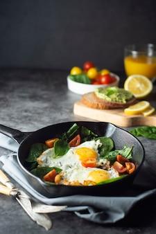 Ovos ensolarados fritos com espinafre, torradas de abacate e tomate fresco, café da manhã saudável