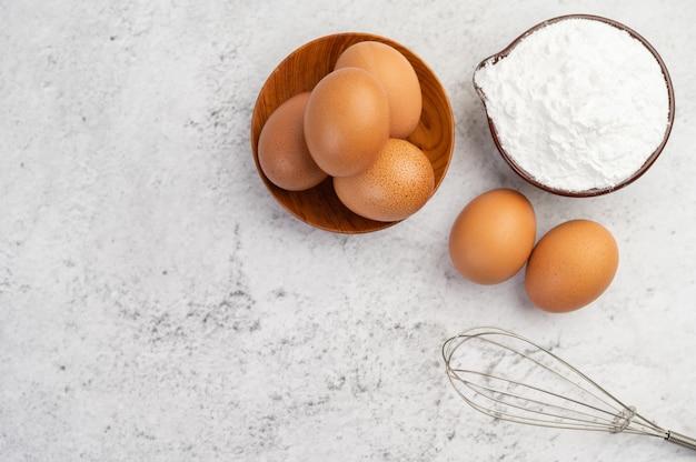 Ovos, farinha de tapioca em um copo e batedor de ovos.