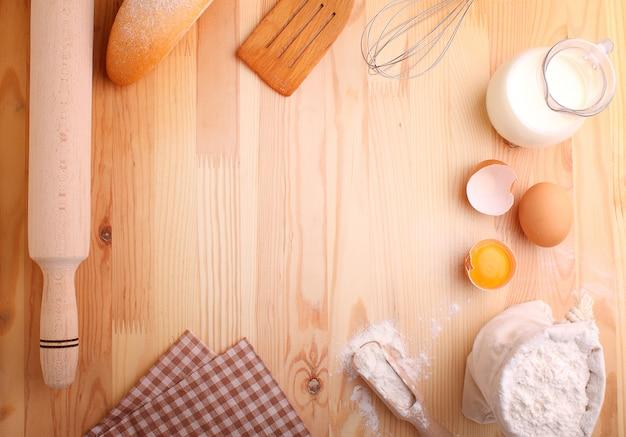 Ovos farinha leite e bata em um fundo de madeira