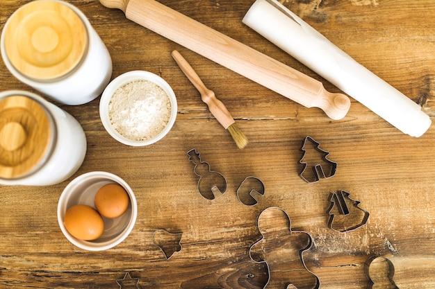 Ovos, farinha, rolo e formas para biscoitos
