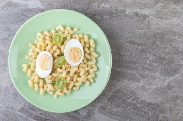 Ovos fatiados e macarrão na placa verde.