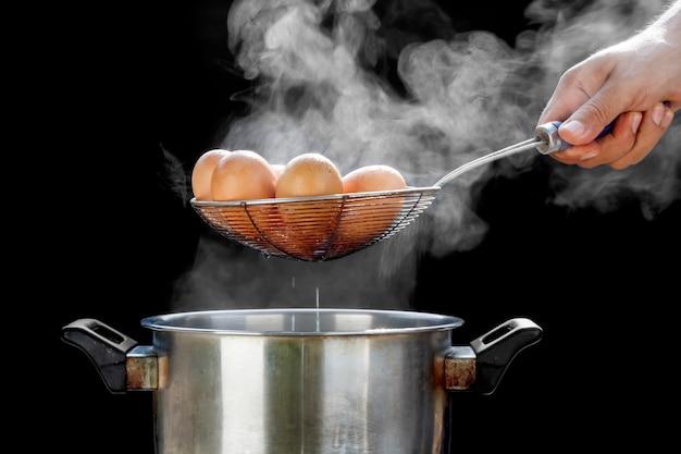 Ovos fervendo em panela de aço inoxidável