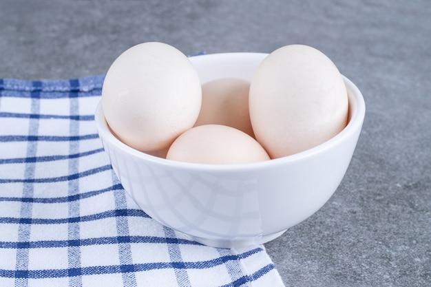 Ovos frescos de galinha branca em um prato branco