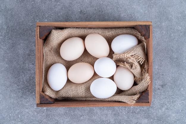 Ovos frescos de galinha branca em uma cesta de madeira
