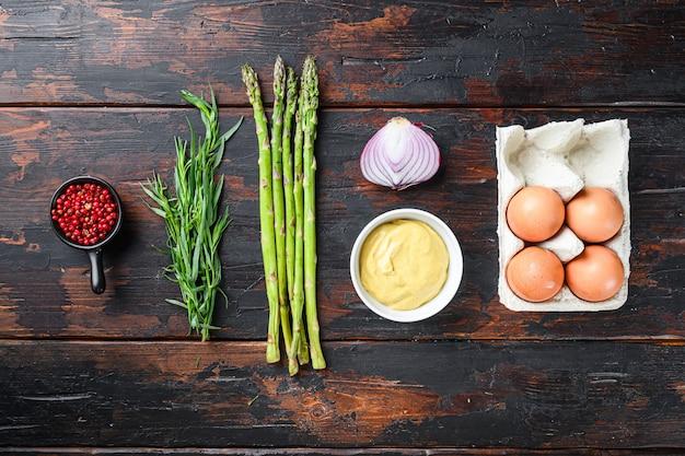Ovos frescos do aspargo e ingredientes franceses do molho com mostarda de dijon, taragon da cebola no fundo velho de madeira escuro, vista superior.