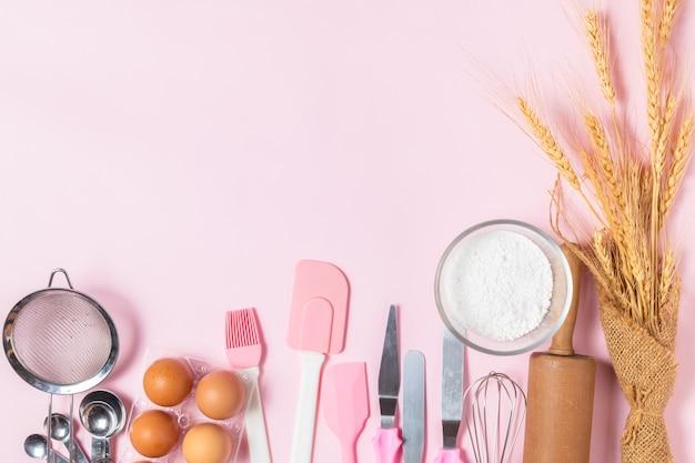 Ovos frescos e farinha de bolo com utensílios de cozinha para bolos em fundo rosa, prepare-se para fazer bolo e conceito de padaria