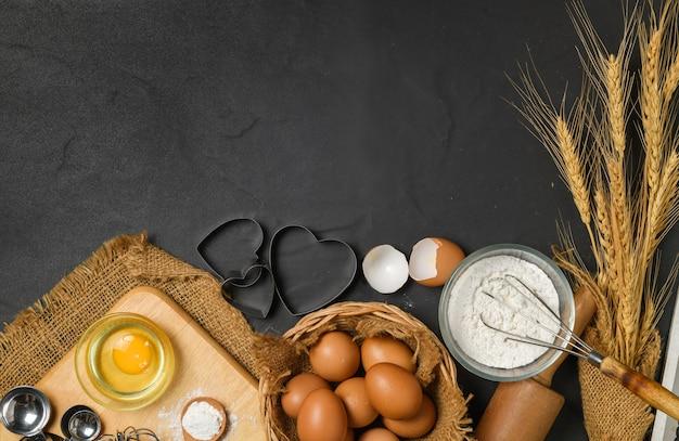 Ovos frescos e farinha de bolo com utensílios de cozinha para bolos na mesa preta, prepare-se para fazer bolo e conceito de padaria